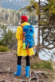 山の湖の近くの丘の上に立って、赤い帽子をかぶっているアクティブな女性ハイカーの全身ショット