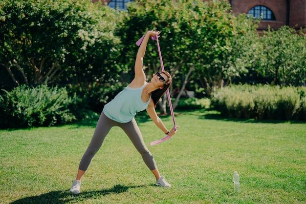アクティブな女性のフルレングスのショットは、フィットネスガムで腕を伸ばし、柔軟性が高く、tシャツのレギンスを着用し、スニーカーは夏の間、屋外の緑の芝生で抵抗バンドのポーズでトレーニングを行います