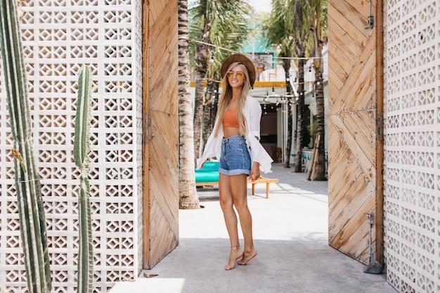 Снимок очаровательной девушки с милой улыбкой в полный рост на курорте. открытый портрет беззаботной светловолосой дамы в джинсовых шортах, танцующей в летний день.