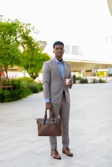 テイクアウトコーヒーのカップを運ぶ屋外のアフリカのビジネスマンのフルレングスショット