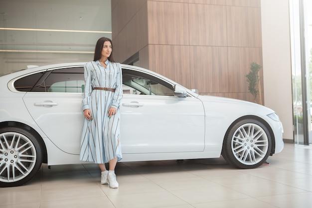 自動車販売店、コピースペースで彼女の新しい自動車でポーズをとるエレガントな女性の全身ショット