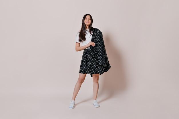 Азиатская женщина в стильном наряде в полный рост на изолированной стене