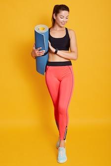 Полная длина выстрел привлекательная молодая женщина с коврик для йоги
