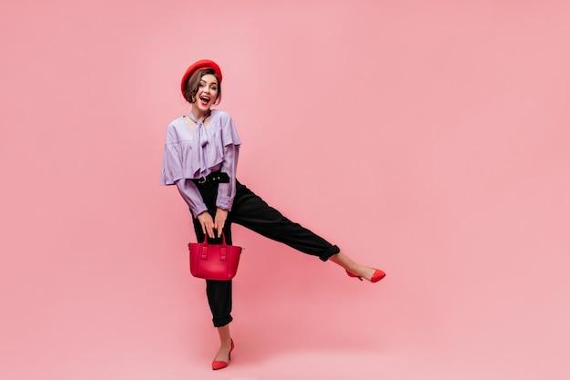 Снимок в полный рост красивой девушки в черных штанах, фиолетовом топе и берете. женщина улыбается, держит сумку и поднимает ногу на розовом фоне.