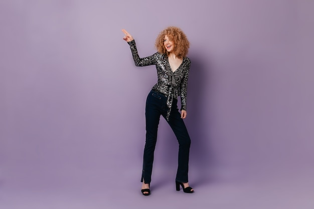 Снимок в полный рост красивой девушки в темных джинсовых штанах и блузке в блестках, танцующей на лиловом пространстве.