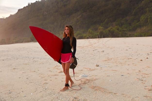 Снимок в полный рост красивой девушки-серфера, одетой в морские шорты и черный непромокаемый топ