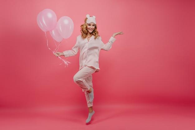 회색 양말 포즈에서 생일 소녀의 전체 길이 샷. 핑크 풍선 점프 실크 잠 옷에 웃는 젊은 아가씨의 초상화.