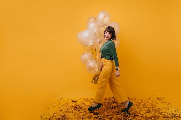 유행 바지에 생일 소녀의 전체 길이 샷. 파티 풍선과 함께 재미 사랑스러운 갈색 머리 모델의 실내 사진.
