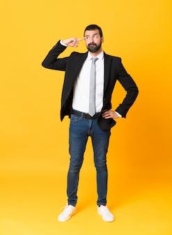 頭に指を置く狂気のジェスチャーを作る分離された黄色の上のビジネスの男性の全身ショット