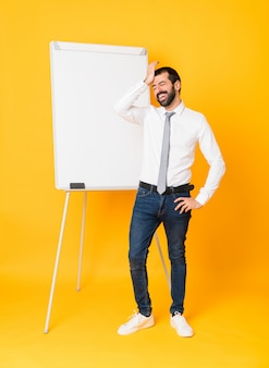 孤立した黄色の上にホワイトボードでプレゼンテーションを行うビジネスマンの全身ショットは、何かを実現し、解決策を意図