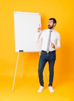 指を上向きのアイデアを考えて黄色の上にホワイトボードでプレゼンテーションを行う実業家の全身ショット