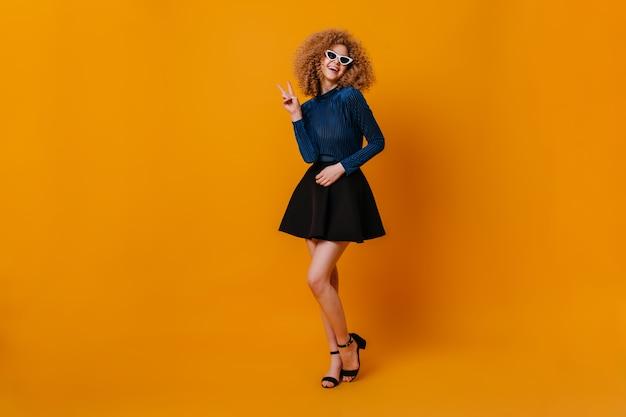 파란색 상단, 치마 및 굽된 샌들을 입고 매력적인 금발 소녀의 전체 길이 샷. 선글라스에 레이디는 노란색 공간에 평화 기호를 보여줍니다.