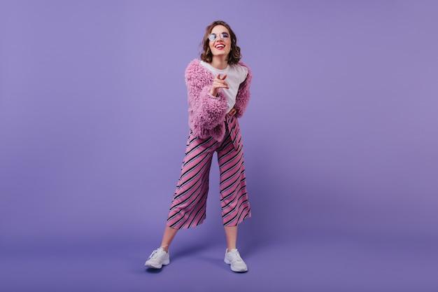 행복을 표현하는 핑크색 바지에 매력적인 곱슬 머리 여인의 전신 샷. 웃는 백인 여자의 실내 사진은 흰색 운동화를 착용합니다.
