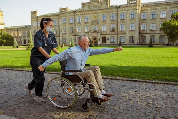 散歩でスーパーマンのジェスチャーをしている患者を回復している元気な老人の全身ショット