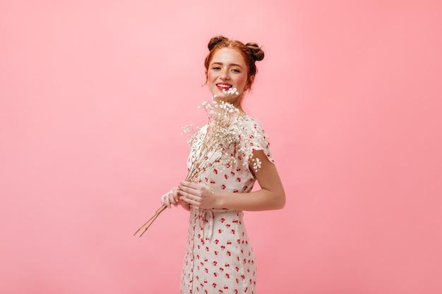 ミディドレスとヒールサンダルでかわいい女性のフルレングスのショット。ピンクの背景に白い花を保持している女性。