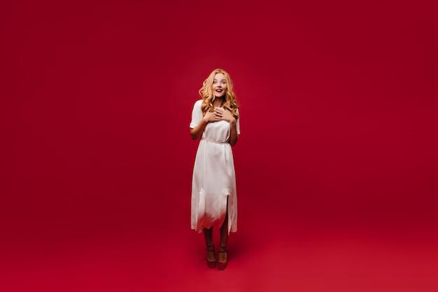 Полнометражный снимок милой романтичной женщины. портрет жизнерадостной кавказской девушки в длинном белом платье.