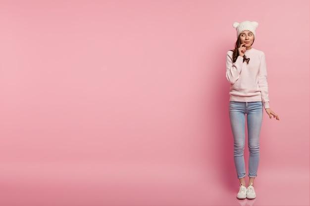 꿈꾸는 유럽 여성의 전체 길이 샷은 입술 근처에 손을 유지하고 옆으로 보이며 사려 깊은 표정을 가지고 있으며 귀에 재미있는 모자를 쓰고 있습니다.