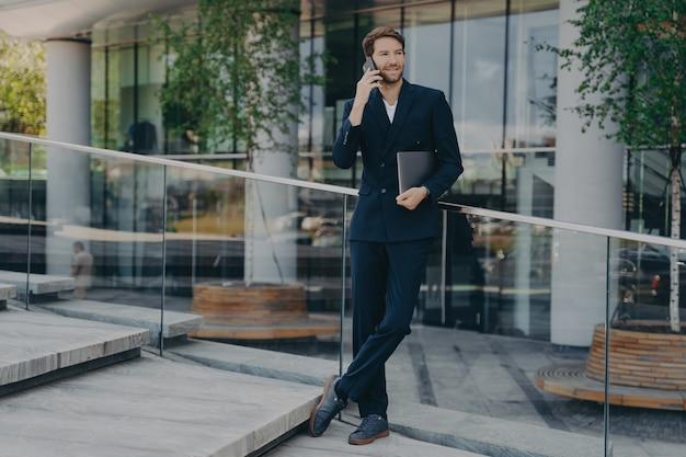 Элегантный бизнесмен в строгой одежде в полный рост разговаривает по телефону