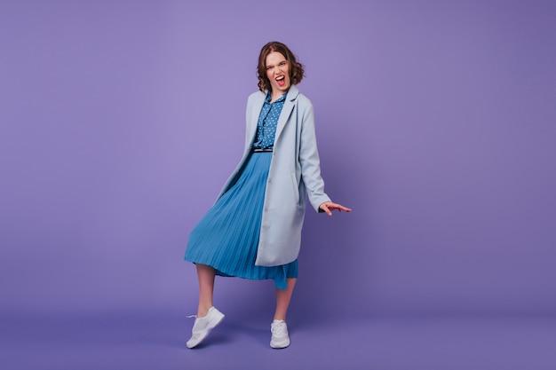 В полный рост взволнованная кудрявая женщина в длинном платье корчит рожи на фиолетовой стене. симпатичная брюнетка девушка позирует в синем пальто и улыбается.
