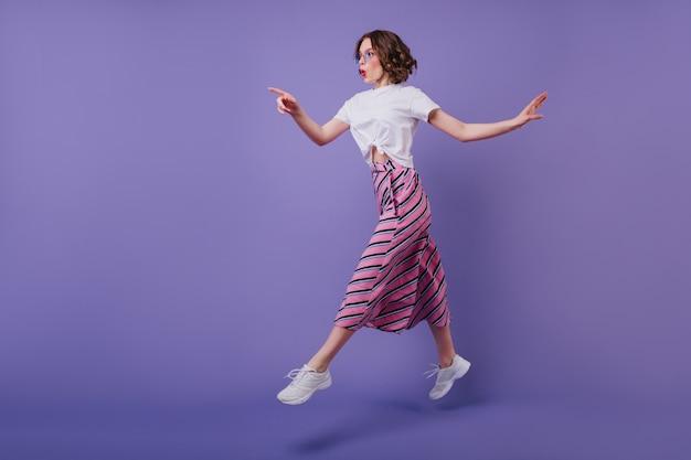 紫色の壁にジャンプする波状の髪型を持つ興奮したかわいい女の子のフルレングスのショット。写真撮影を楽しんでいるスニーカーのスタイリッシュな気さくな女性。