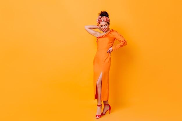 オレンジ色の空間でポーズをとる彼女の頭の上にスリットとスカーフを備えた長いシルクのドレスを着たファッショナブルな女性のフルレングスのショット。