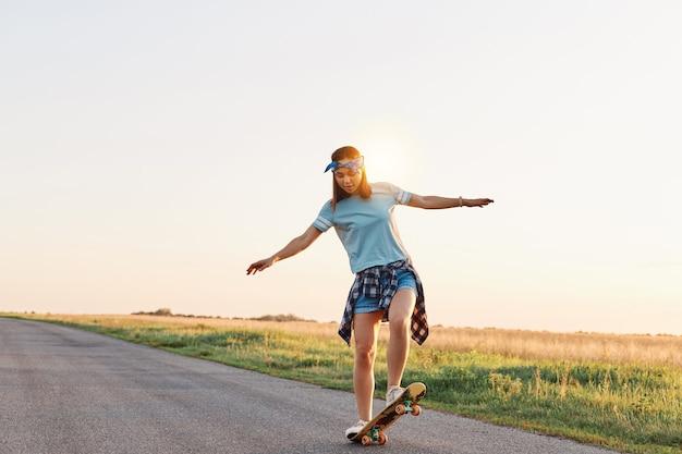 何もない通りでカジュアルな服装のスケートボードを着て、手を脇に広げ、乗馬を楽しんで、顔の表情を集中させている女の子の全身ショット。
