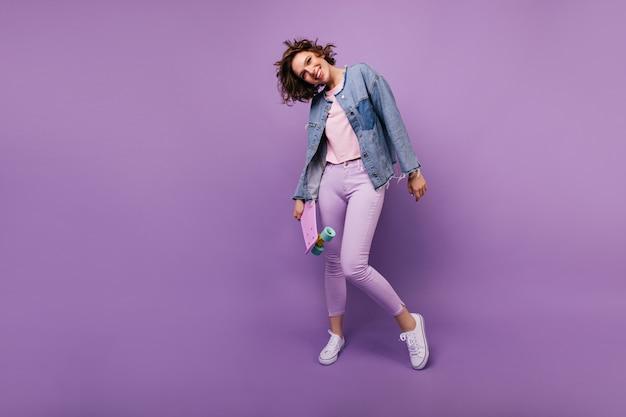 Снимок в полный рост гламурной европейской модели в фиолетовых штанах. крытая фотография довольно кавказской девушки с короткой стрижкой позирует.