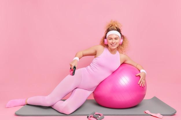 Снимок в полный рост счастливой кудрявой женщины, которая использует массажер для тела, занимается фитнесом, опирается на швейцарский мяч, одетый в спортивную одежду, позирует на коврике, слушает музыку в наушниках, изолированных на розовой стене