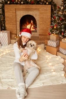 스마트 폰과 개를 손에 든 행복한 여성의 전체 길이 사진, 회색 바지, 흰색 스웨터, 산타클로스 모자를 쓴 여성, 크리스마스 트리와 벽난로 근처의 축제 공간에서 포즈를 취한 여성.