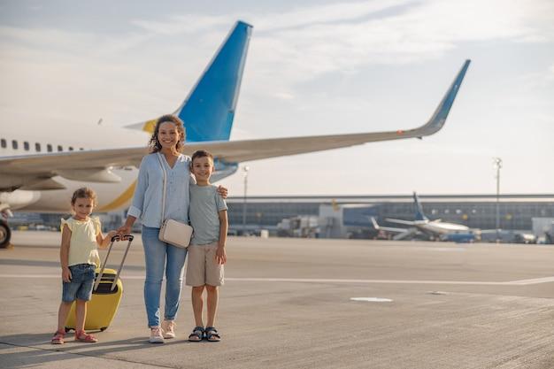 Снимок в полный рост счастливой матери с двумя маленькими детьми, улыбаясь в камеру, стоя перед большим самолетом в дневное время. семья, отдых, концепция путешествия