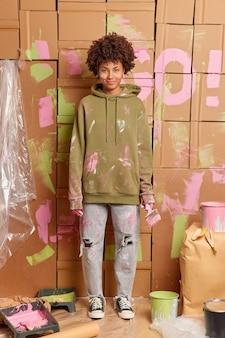 Снимок в полный рост, как счастливая женщина-декоратор красит стены, обновляет интерьер комнаты, одетая в повседневную одежду, стоит, залитую краской, с использованием различных инструментов. концепция ремонта и обслуживания квартиры