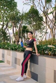 공원에 물병이 서 있는 건강한 젊은 여성의 전체 길이 샷.