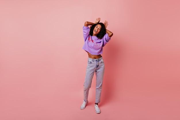 초상화 촬영 중에 농담하는 영감을받은 흑인 소녀의 전체 길이 샷. 분홍색에 재미 있은 얼굴을 만드는 평온한 곱슬 여자.