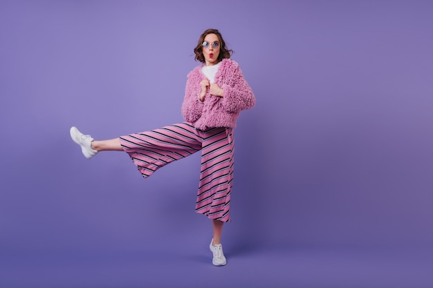 片足で立っているインスピレーションを得た黒髪の女の子のフルレングスのショット。紫の壁にキスの表情でポーズをとって驚きを表現する白人女性。