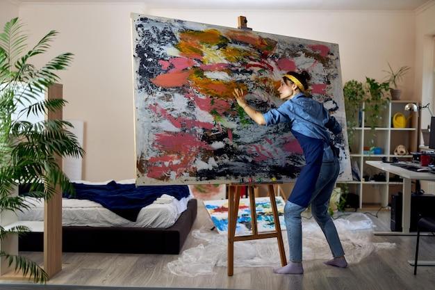Полноразмерный снимок вдохновленной художницы, работающей над большой современной абстрактной картиной маслом