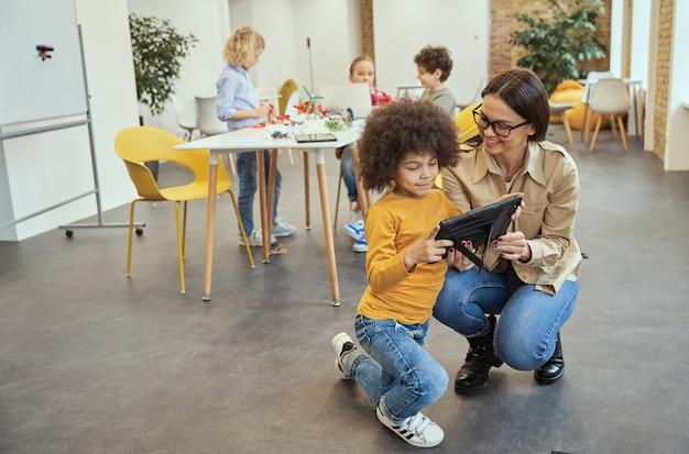 Добрая молодая учительница улыбается, показывая ей видео на планшетном пк в полный рост