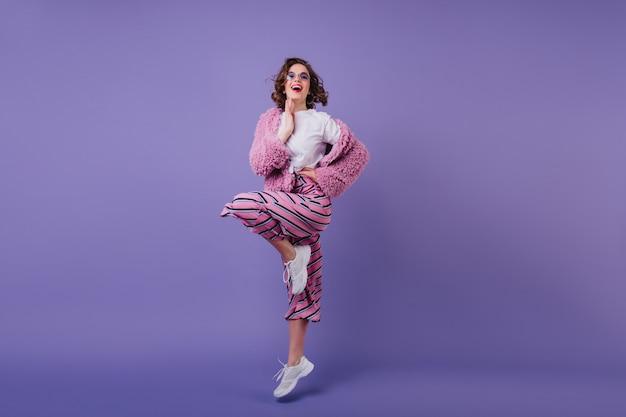 白いスニーカーでジャンプする素敵な女の子を笑うフルレングスのショット。片足で立っているピンクの服装で満足しているブルネットの女性の写真。