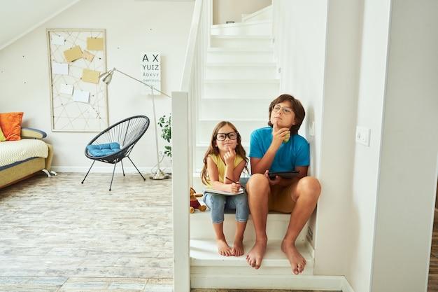 自宅の階段に座って眼鏡をかけている弟と妹の全身ショットと