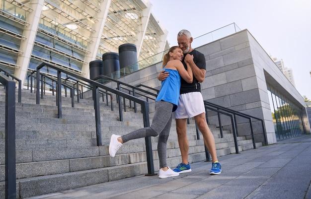 Снимок в полный рост очаровательной спортивной пары среднего возраста, мужчины и женщины в спортивной одежде, обнимающихся