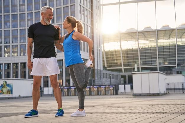 성숙한 커플 스포티한 남자와 여자가 야외에서 함께 운동하는 사랑스러운 전체 길이 샷