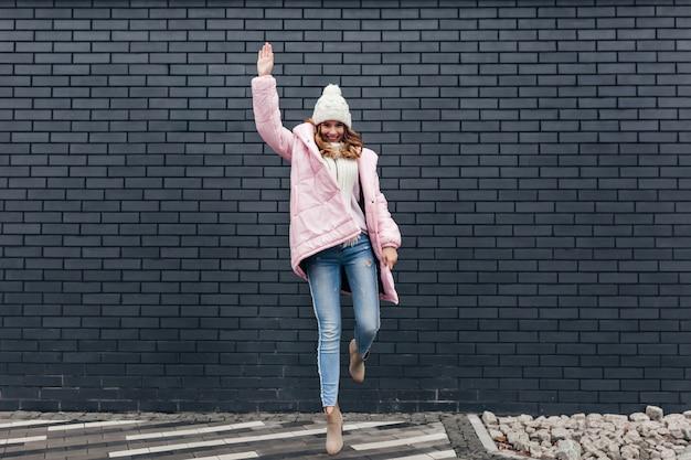 ジーンズと冬のアクセサリーで壮大な女の子のフルレングスのショット。都会の通りで踊っている格好良い金髪の女性の屋外の肖像画。