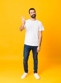 격리 된 노란색 행복과 손가락으로 세 세 이상 수염을 가진 남자의 전체 길이 샷