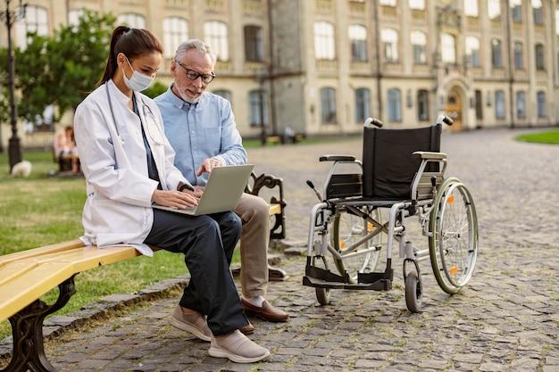 近くの公園のベンチに座っている車椅子で成熟した回復中の患者の全身ショット