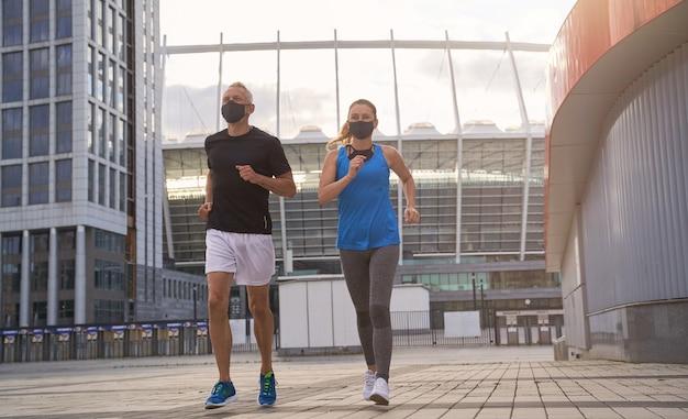 Снимок в полный рост здоровой пары средних лет в защитных масках, бегающих вместе по утрам
