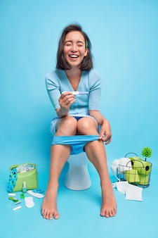 陽性の若いアジア人女性の全身ショットは妊娠検査を保持し、陽性の結果が得られ、将来のマタニティウェアがバスルームの青い壁のトイレでジャンパー溺死したパンティーのポーズを着ていることがわかります