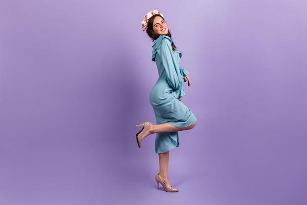 かかととミディドレスのポジティブな若いブルネットのフルレングスのショット。ライラックの壁に笑みを浮かべて彼女の髪に花を持つ女性モデル。