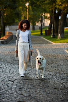 Полнометражный снимок довольно здоровой молодой леди, идущей утром в парке с собакой