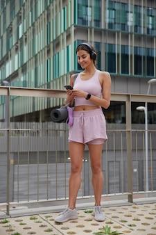 アクティブウェアのスニーカーを身に着けたジムに歩いて行くかわいいスポーツウーマンのフルレングスのショットは、スマートフォンを介して友人とメッセージを送信し、橋の上の屋外に立っているヘッドフォンで音楽を聴きます。人とライフスタイル