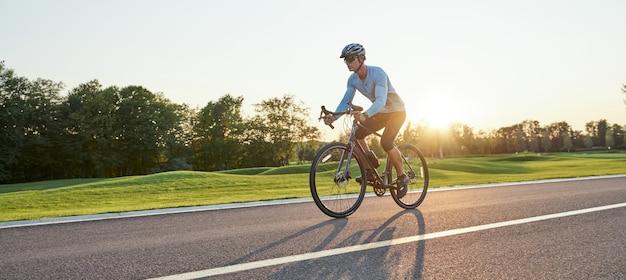 Полнометражный снимок профессионального гонщика-мужчины в спортивной одежде и шлеме, тренирующем езду на шоссейном велосипеде