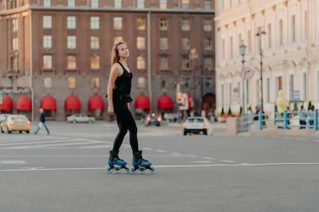 Снимок в полный рост стройной темноволосой женщины на роликах по асфальтированной дороге, одетой в черную спортивную одежду, которая наслаждается упражнениями на свежем воздухе для здорового и сильного тела. концепция спорта и хобби